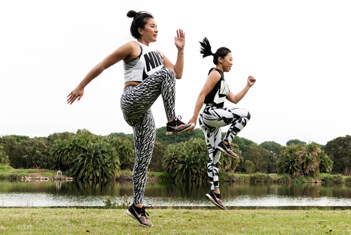 Two girls are doing a proper dynamic warm up prior to their run.