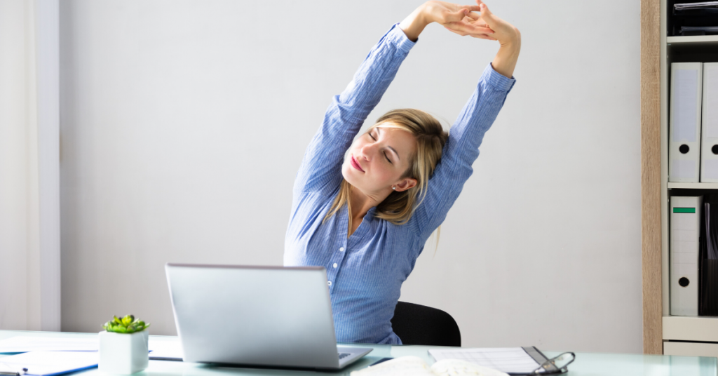 Woman is stretching throughout her day to prevent prolonged postures.